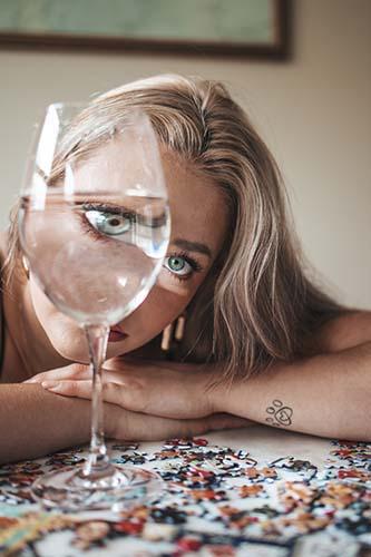 Frau die durch ein Wasserglas blickt